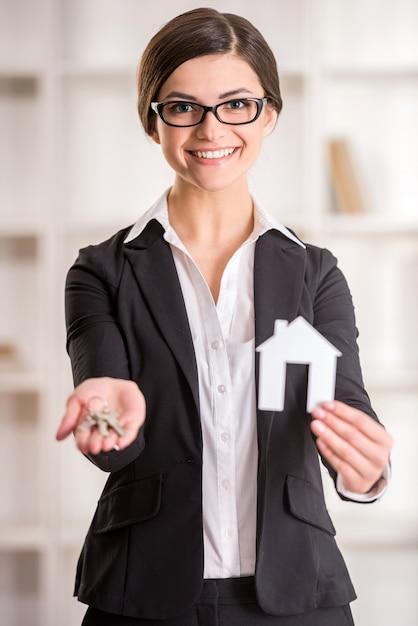 Femme agent immobilier montre maison pour signe de vente et clés. Photo Premium
