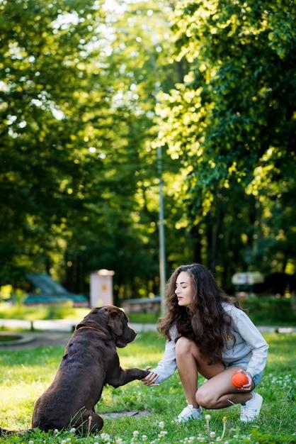 Femme agitant la patte de son chien dans le jardin Photo gratuit