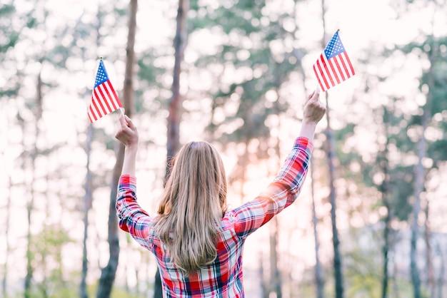 Femme agitant de petits drapeaux américains à l'extérieur Photo gratuit