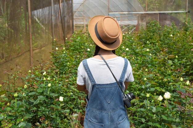 Femme agricole tenant une tablette dans la roseraie. Photo gratuit