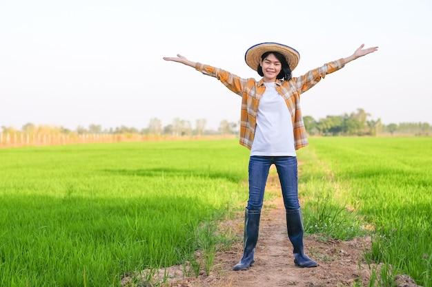Femme D'agriculteur Asiatique Debout Et Lever La Main à La Ferme De Riz Photo Premium