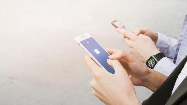 Femme à L'aide De L'application Facebook Sur Mobile Près De L'homme Portant Une Montre Intelligente Photo gratuit