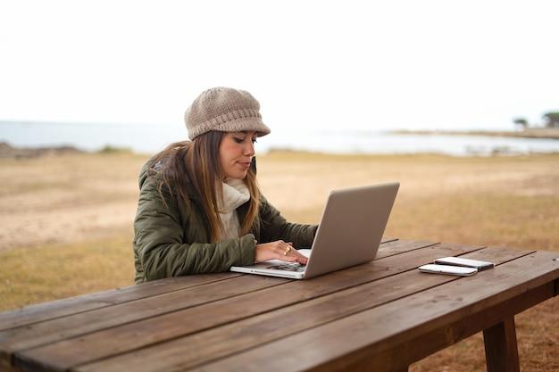 Femme à L'aide D'une Connexion Internet En Plein Air, Assis à Une Table En Bois Dans Un Parc Marin Travaillant à Un Ordinateur Portable Photo Premium