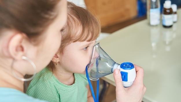 La femme aide à respirer à travers le masque à l'enfant Photo Premium