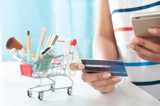 Femme à L'aide De Smartphone Et De Carte De Crédit, Shopping Des Articles De Beauté. Achat En Ligne, Paiement électronique Photo Premium