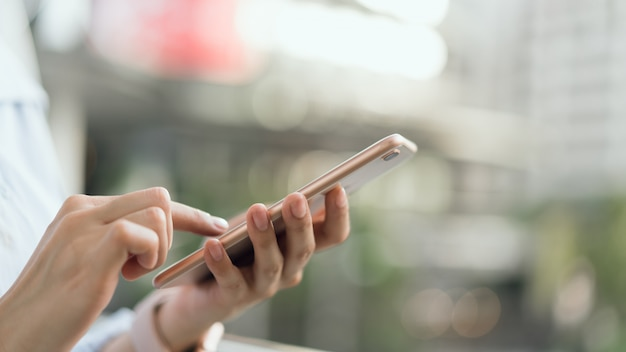 Femme à l'aide de smartphone sur l'escalier dans les espaces publics, pendant les loisirs. Photo Premium