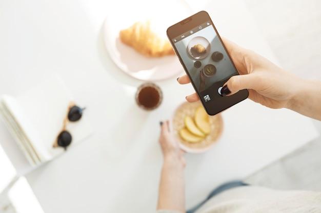 Femme à L'aide D'un Smartphone Pour Prendre Une Photo De Son Repas Photo gratuit