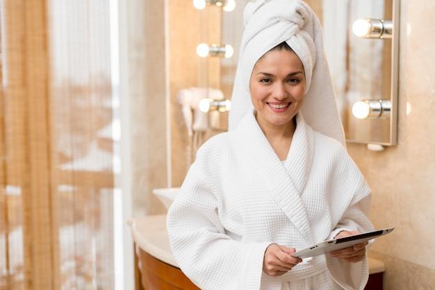 Femme à l'aide d'une tablette dans une chambre d'hôtel Photo gratuit