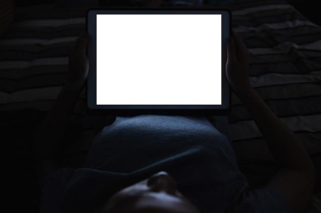 Femme à L'aide De Tablette Numérique La Nuit Sur Le Lit, Avec écran Blanc Vide Vide Photo Premium