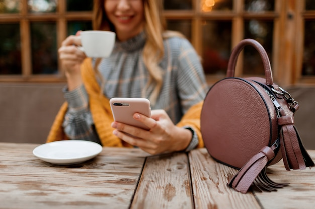 Femme à L'aide De Téléphone Portable, Sms Et Boire Du Café. Sac élégant Sur Table. Porter Une Robe Grise Et Un Plaid Orange. Bénéficiant D'une Matinée Agréable Au Café. Photo gratuit