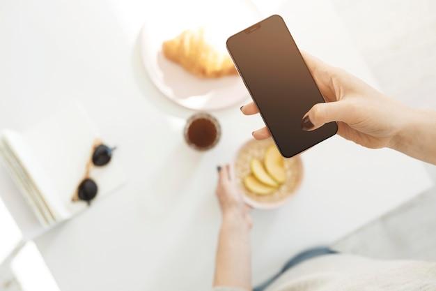 Femme à L'aide D'un Téléphone Pour Prendre Une Photo De Son Repas Photo Premium