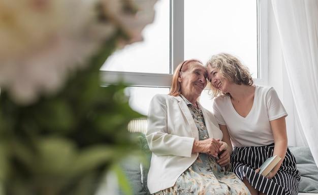 Femme aimante avec sa grand-mère assise sur un canapé à la maison Photo gratuit