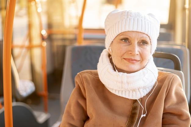 Femme aînée dans un bus écoutant de la musique Photo gratuit