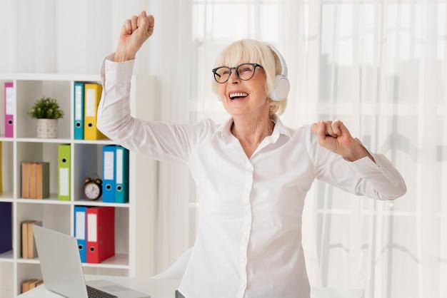 Femme aînée écoutant de la musique dans son bureau Photo gratuit