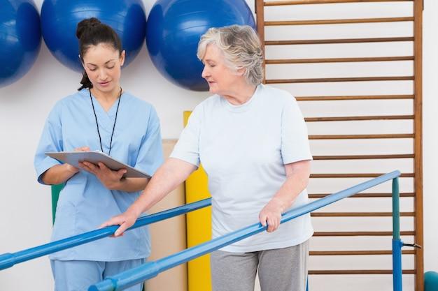 Femme aînée, marche, à, barres parallèles, à, thérapeute Photo Premium