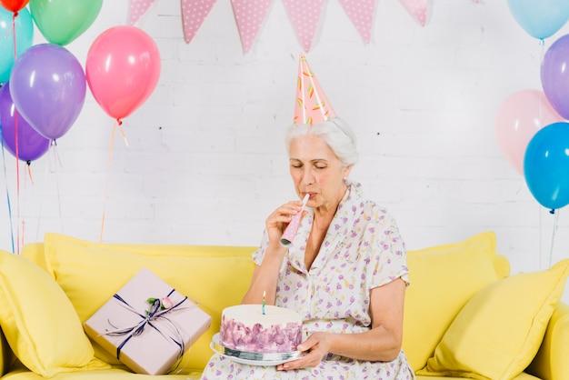 Femme aînée, regarder, anniversaire, souffler corne fête Photo gratuit