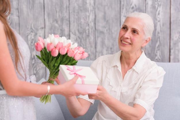 Femme aînée souriante recevant un bouquet de fleurs et une boîte-cadeau devant son petit-enfant Photo gratuit