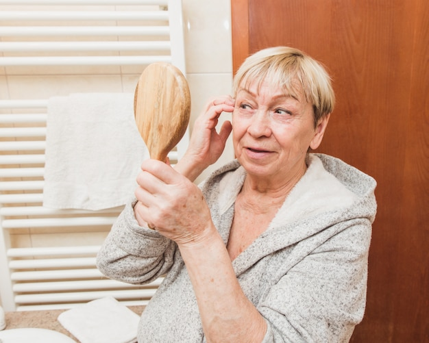 Femme aînée, toucher, elle, doux, peau visage, et, regarder, main, miroir, chez soi Photo Premium