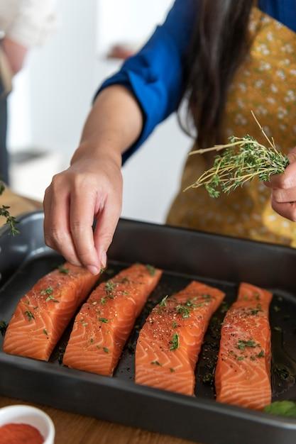 Femme ajoutant des épices et des herbes au saumon cru Photo gratuit