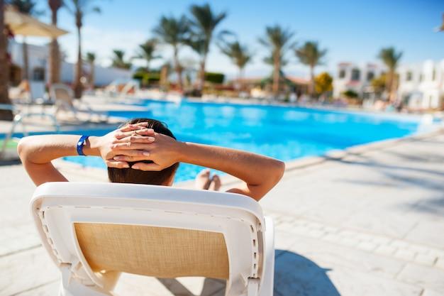 Femme allongée sur une chaise longue au bord de la piscine bleue Photo Premium
