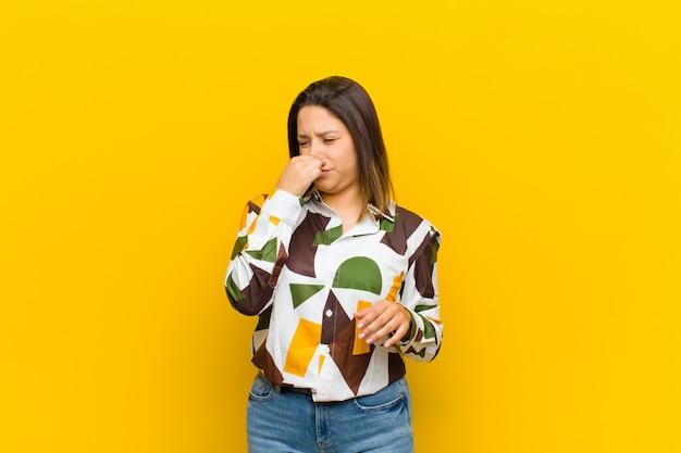 Femme d'amérique latine se sentant dégoûté, tenant le nez pour éviter de sentir une puanteur fétide et déplaisante isolée contre un mur jaune Photo Premium