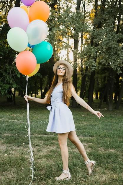 Femme d'anniversaire enjouée avec des ballons Photo gratuit