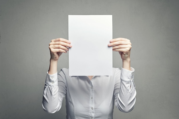 Femme anonyme couvrant le visage avec une feuille de papier Photo Premium