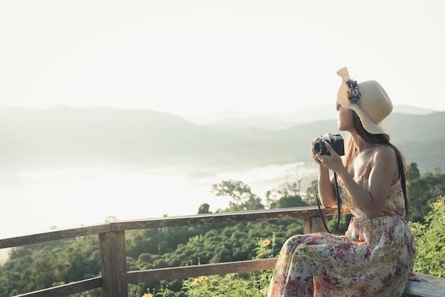 Une Femme Avec Un Appareil Photo Pour Voir La Vue Sur La Montagne Photo gratuit