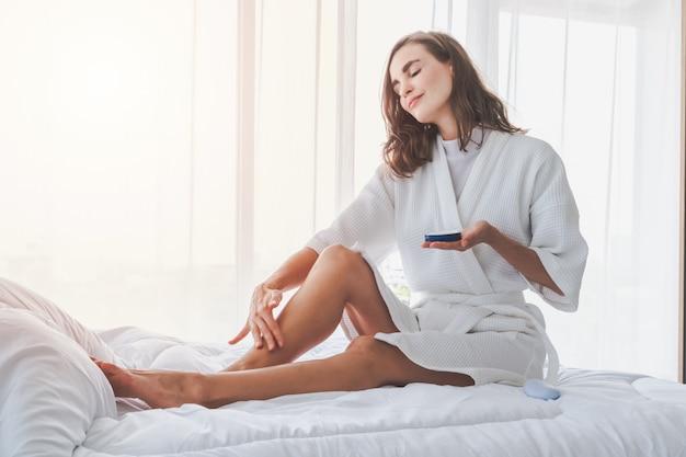 Femme appliquant une crème rafraîchissante ou une lotion pour le corps sur ses jambes et ses mains Photo Premium