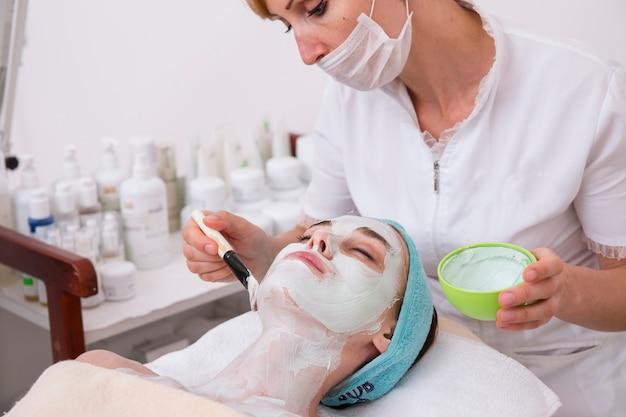 Femme appliquant un masque à un client Photo gratuit