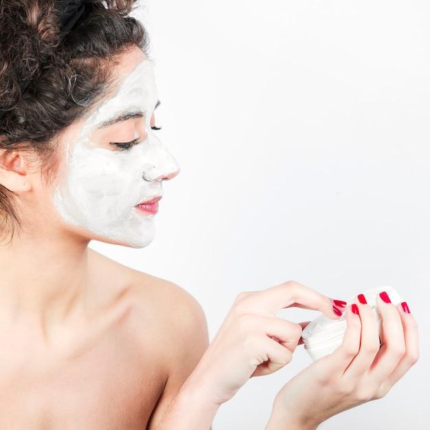 Femme appliquant un masque facial sur son visage sur fond blanc Photo gratuit
