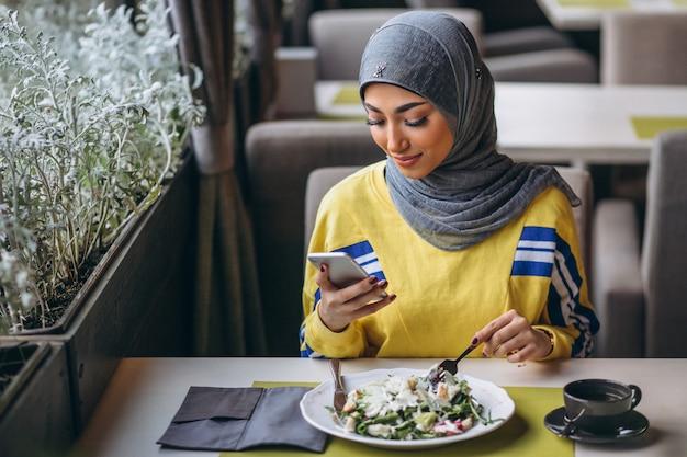 Femme arabe en hijab à l'intérieur d'un café mangeant une salade Photo gratuit