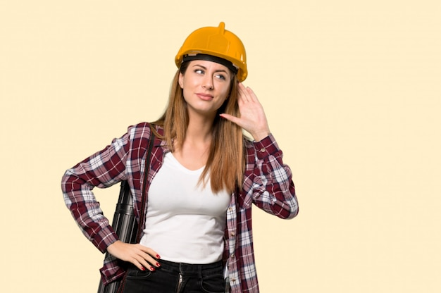 Femme architecte écoute quelque chose en mettant la main sur l'oreille sur un mur jaune isolé Photo Premium