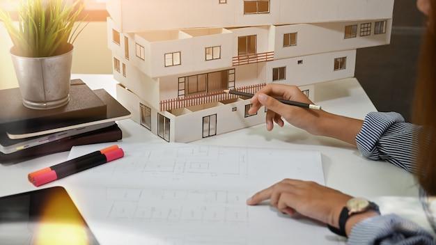 Femme architecte travaillant avec maison modèle et blueprint au bureau à domicile. Photo Premium