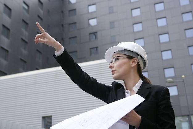 Femme architecte travaillant en plein air avec des bâtiments Photo Premium
