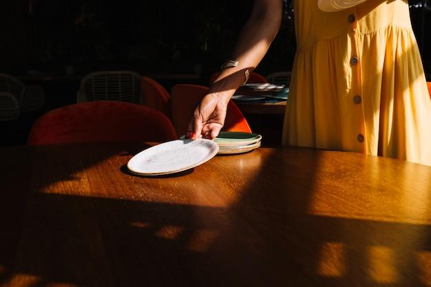 Femme arrangeant les assiettes sur une table en bois Photo gratuit