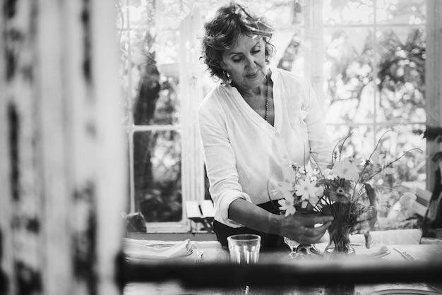 Femme arrangeant des fleurs dans une serre Photo gratuit