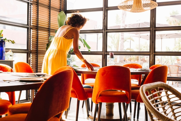 Femme arrangeant la vaisselle sur la table du restaurant Photo gratuit
