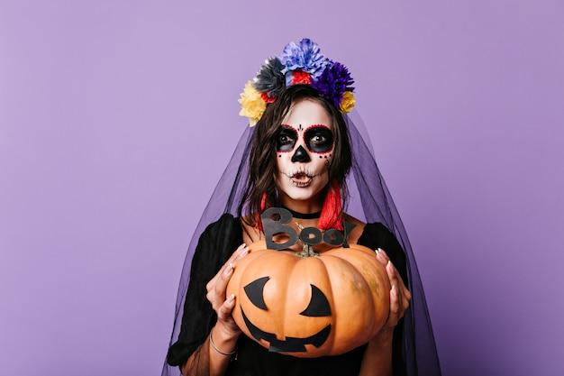 Une Femme à L'art Du Visage à La Mexicaine Essaie De Faire Peur. Brune à La Citrouille Et Voile De Mariage Noir Posant Sur Un Mur Lilas. Photo gratuit