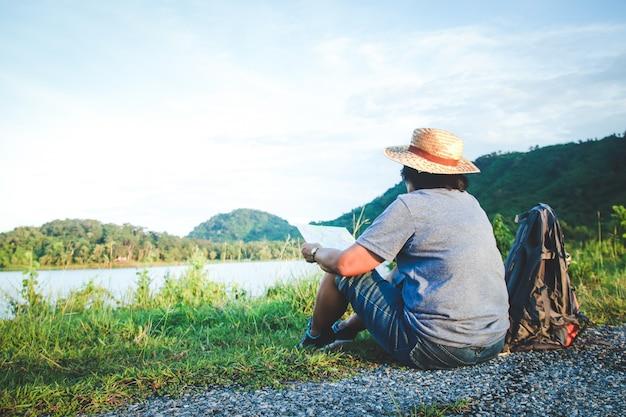 Une Femme Asiatique âgée Porte Un Chapeau Assis Sur L'herbe Pour Voir Une Carte Du Tourisme De Nature. Photo Premium
