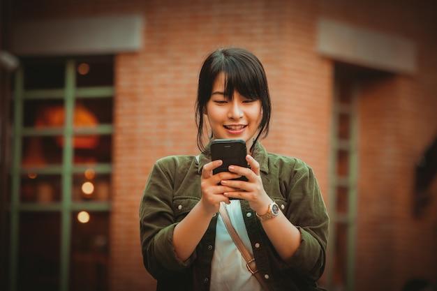 Femme asiatique à l'aide de smartphone avec bonne humeur au centre commercial Photo Premium
