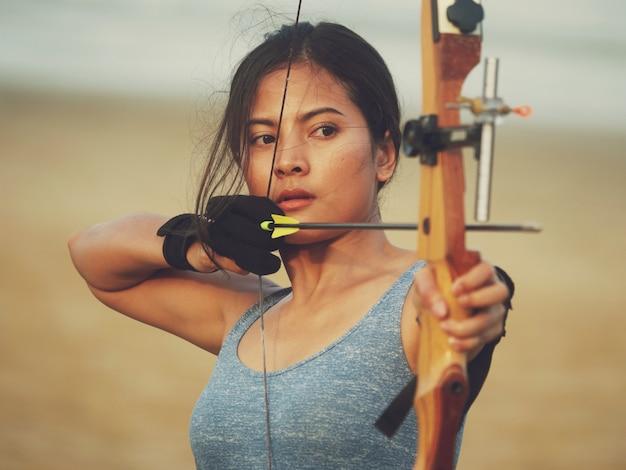 Femme asiatique avec arc tir à l'arc Photo Premium