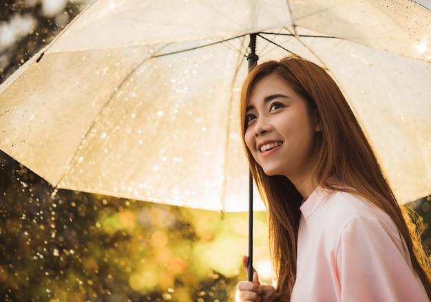Femme asiatique attendait la pluie, elle avait un parapluie. Photo Premium