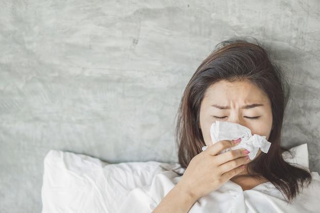 Femme asiatique, avoir, grippe, et, éternuer, lit Photo Premium