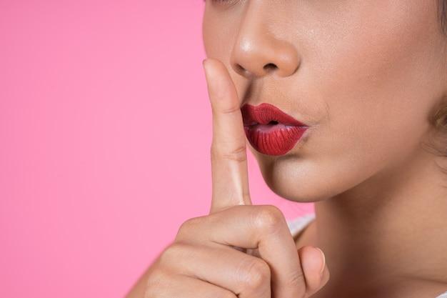 Femme asiatique beauté lèvres rouges et doigt montrant signe de silence chut Photo gratuit