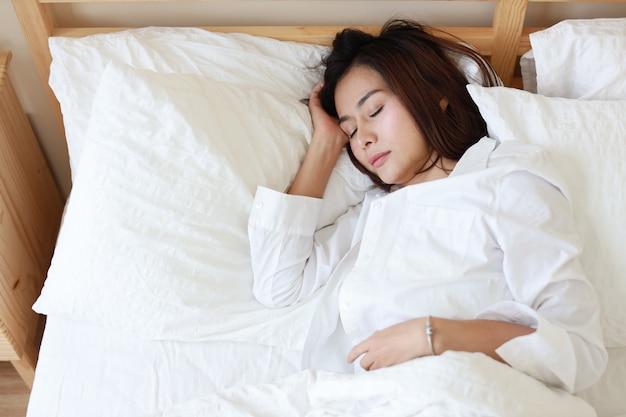 Femme asiatique belle et en bonne santé, dormant sur un lit blanc dans la chambre Photo Premium