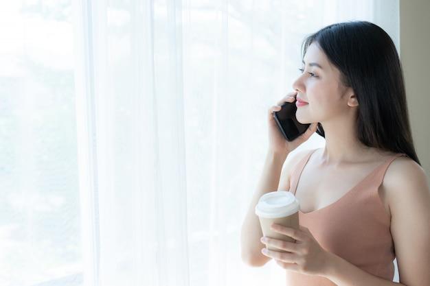 Femme asiatique belle fille mignonne jouant un téléphone intelligent dans la chambre blanche du matin Photo gratuit