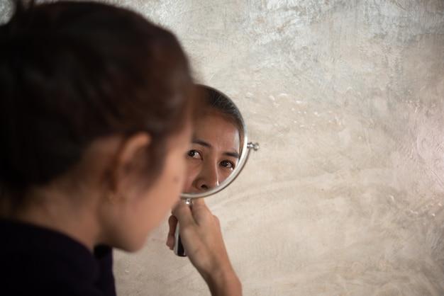 Femme asiatique brille dans le miroir pour voir les rides et les cheveux gris. Photo Premium