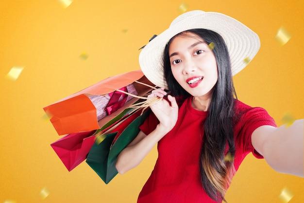 Femme Asiatique Avec Chapeau Portant Des Sacs à Provisions Et Prenant Selfie Sur Vente De Fin D'année. Bonne Année 2021 Photo Premium