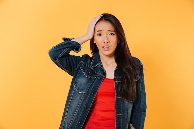 Femme Asiatique Confuse En Veste En Jean Tenant Sa Tête Photo gratuit